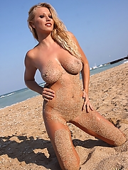 Nikita posing naked in the sand at the beach