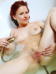 Stunning redhead having fun in a bathtub