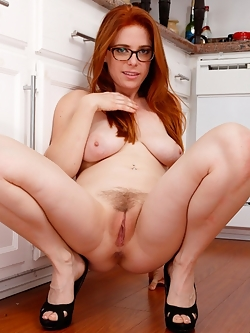 Busty redhead lifts up her dress in the kitchen